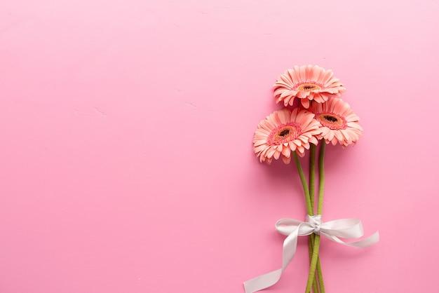 ピンクのガーベラのデイジーブーケとリボン。ミニマルなデザインのフラットレイ。パステルカラー。誕生日おめでとう
