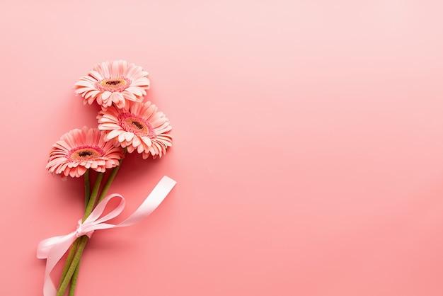 ピンクのガーベラのデイジーブーケとリボン。ミニマルなデザインのフラットレイ。パステルカラー