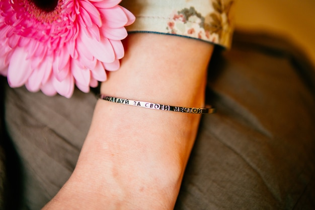 Pink gerbera and woman's hand with metal bracelet