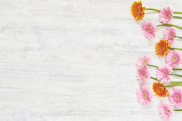 Розовые герберы на белом столе. цветочный стол для поздравления с цветами герберы