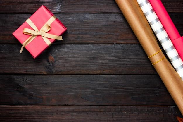 위의 어두운 나무 배경 보기에 분홍색 선물 및 포장지