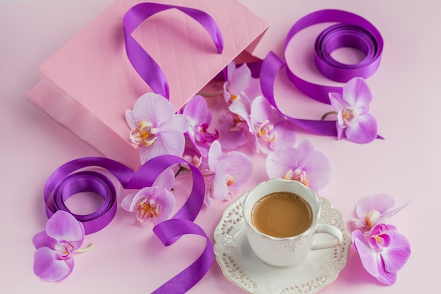 Розовый подарочный пакет и летающие цветы орхидеи на светло-розовом фоне