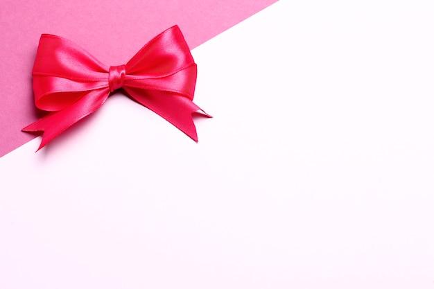 ピンクの背景にピンクのギフトの弓