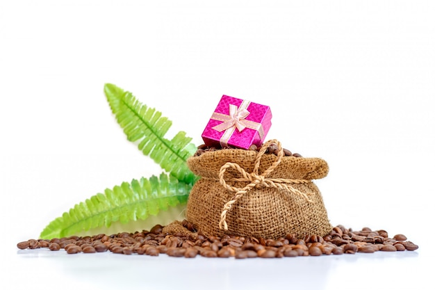 A pink gift box on coffee burlap bag with coffee been isolated white background.