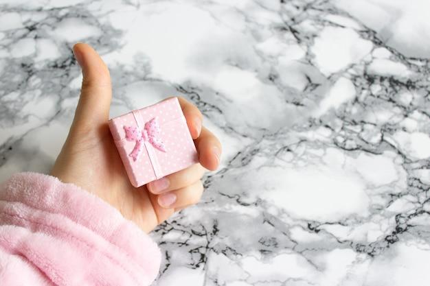 핑크 선물 상자 여성 손 반지 아래 선물 상자를 보유