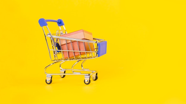 Pink gift box in the miniature shopping cart against yellow background