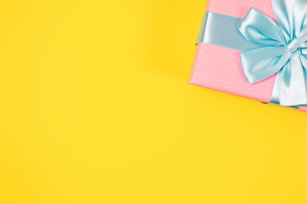 Pink gift box tied with blue ribbon with bow at the top on yellow background. copy space for text. minimal flat lay.