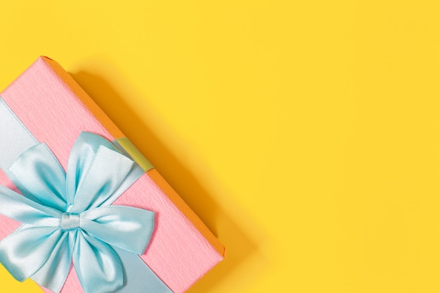 Pink gift box tied with blue ribbon with bow at the top on yellow background. copy space.