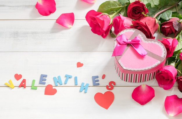 Pink gift box and valentine's text with fresh red rose on white wood background, love and valentine'