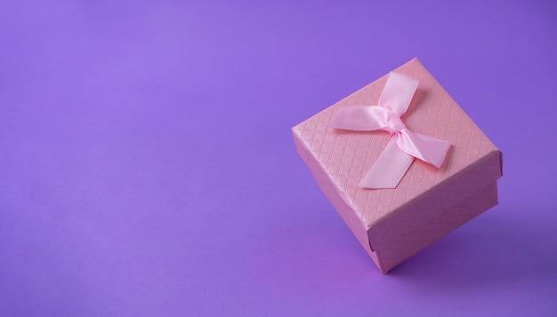 Розовая подарочная коробка с бантом стоит ребро на сиреневом фоне