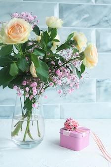 Розовая подарочная коробка с вазой цветов на столе.