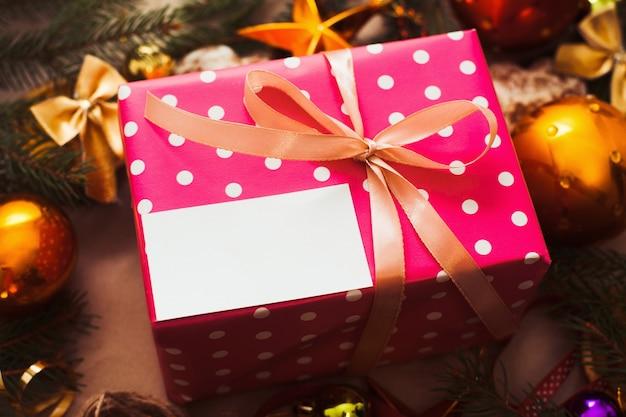 크리스마스 트리 아래 빈 카드와 함께 핑크 선물 상자