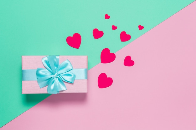 Розовая подарочная коробка с синим бантом на пастельном двухцветном фоне розового и мятного, копией пространства, плоской планировки. 8 марта, 14 февраля, день рождения, концепция празднования дня святого валентина, матери, женского дня. по горизонтали