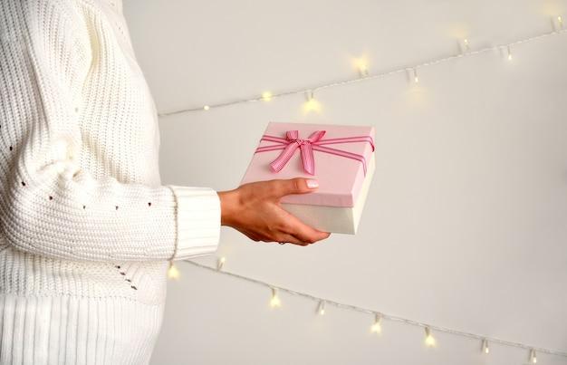 Розовая подарочная коробка с бантом в женской руке в свитере на светлом фоне