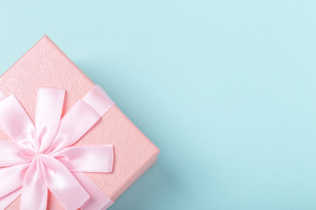 Pink gift box with bow on mint color background. copy space