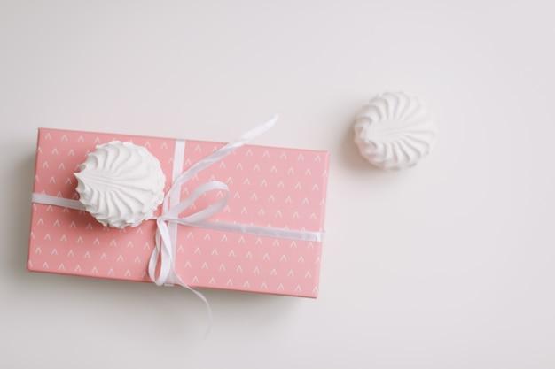 白い表面に弓が付いているピンクのギフトボックス