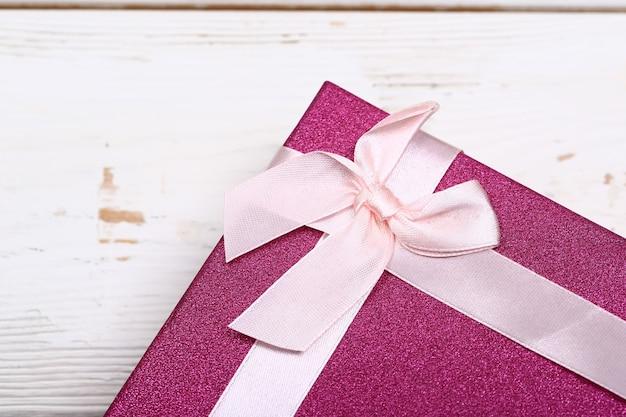 Розовая подарочная коробка с бантом на белом деревянном фоне