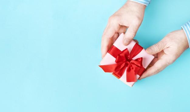 파란색 배경에 남성 손에 붉은 활이 있는 분홍색 선물 상자. 바로 위. 복사 공간