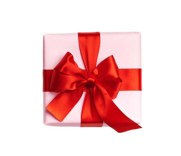 白い背景で隔離の赤い弓とピンクのギフトボックス。上面図。フラットレイ。