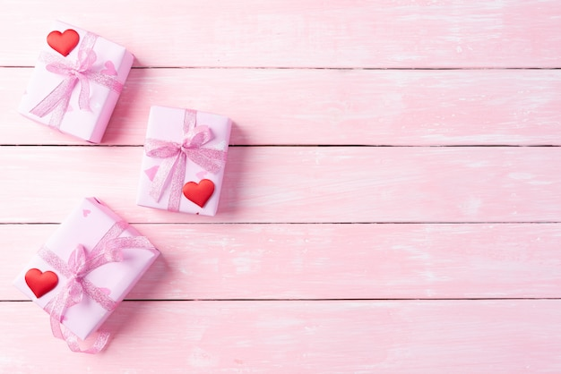 Pink gift box with red heart and flowers on pink wooden background.
