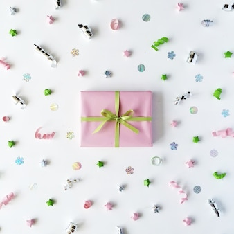 Pink gift box with ribbon and bow on white decorated with tinsel