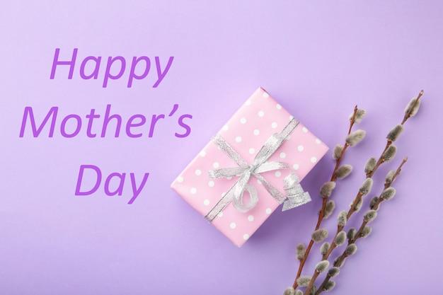 Розовая подарочная коробка с веточками ивы и садом. поздравительная открытка с днем матери. вид сверху