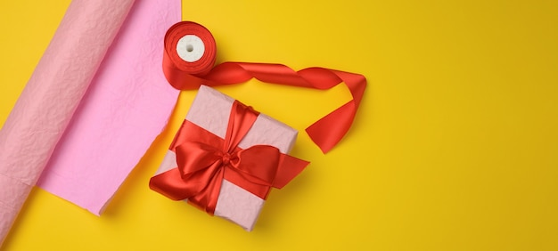 Pink gift box wrapped in red silk ribbon on yellow background, copy space