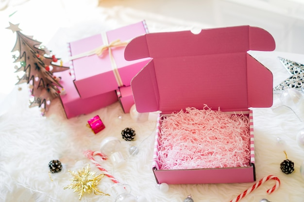 Pink gift boxes open bow ribbon with bright lamp, candy and star on white carpet