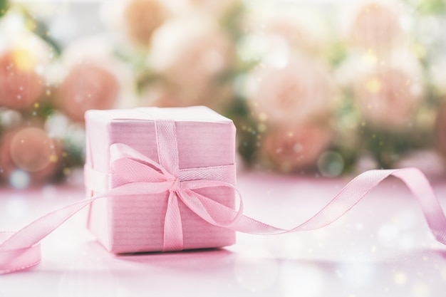 Pink gift or present box pink background.