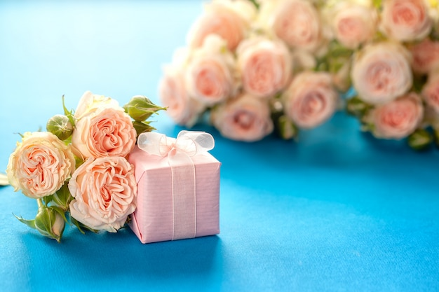 Pink gift or present box and roses flowers on blue b