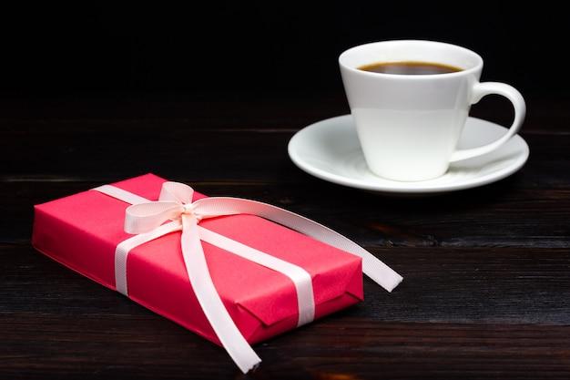 흰색 리본과 어두운 표면에 커피의 흰색 컵 핑크 선물. 소박한 스타일