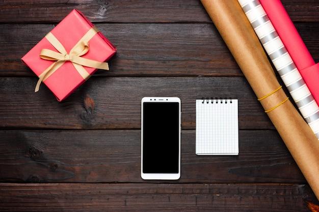 분홍색 선물, 포장지 및 어두운 나무 테이블에 흰색 전화. 위에서 봅니다.