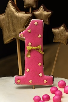 Pink gingerbread with number 1 on a holiday cake on a dark wall. close up