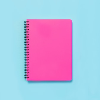Pink girlish school supplies, notebooks on blue. top view, flat lay.
