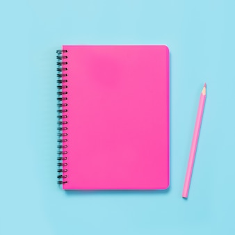 Pink girlish school supplies, notebooks and pens on punchy blue. top view, flat lay. copy space.