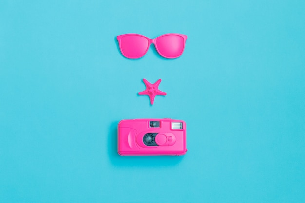 Pink glasses, camera and starfish on blue background