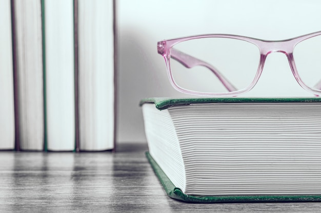 Pink glasses on a thick book in a green cover. row of books