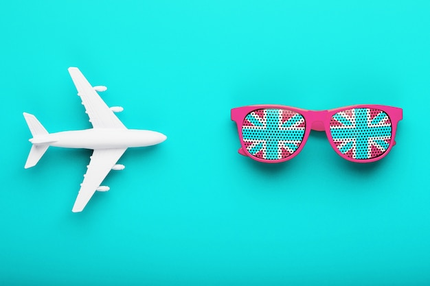 Pink glasses with the flag of the united kingdom in lenses on a blue surface with a white airplane