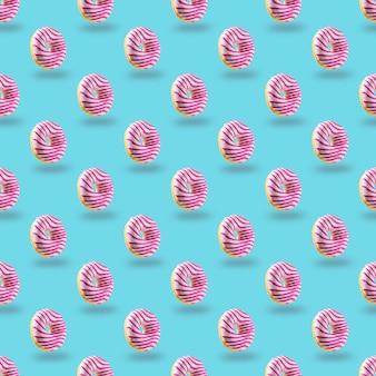 Pink glazed  donut seamless pattern on blue background