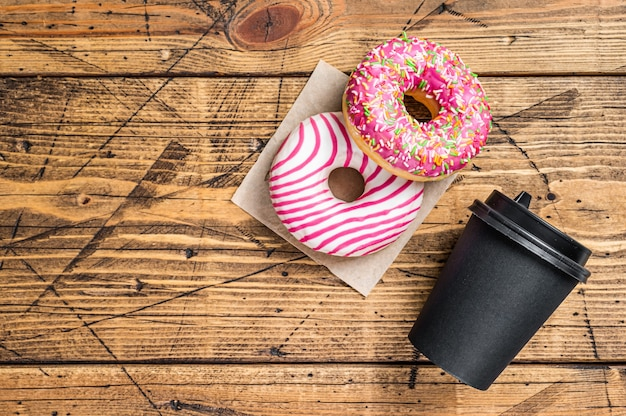 커피와 함께 식탁에 핑크 글레이즈드 도넛. 나무 배경입니다. 평면도. 공간을 복사합니다.