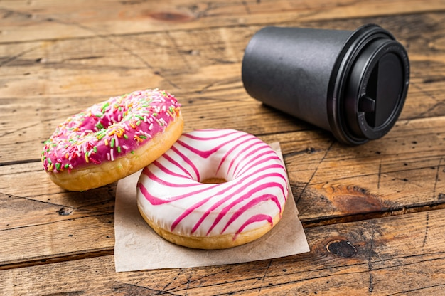 커피와 함께 식탁에 핑크 글레이즈드 도넛. 나무 배경입니다. 평면도.