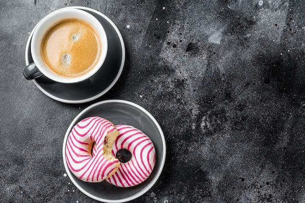 커피 한 잔과 함께 핑크 글레이즈드 도넛, 도넛. 검은 배경. 평면도. 공간을 복사합니다.