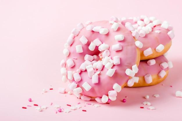 ピンクの背景のクローズアップにマシュマロとピンクの艶をかけられたドーナツ。