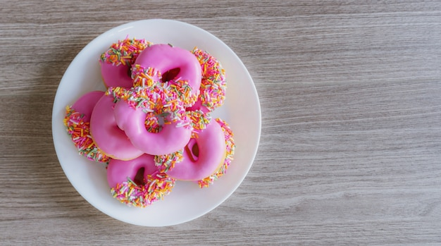 Pink glazed mini donuts in white plate on wooden table