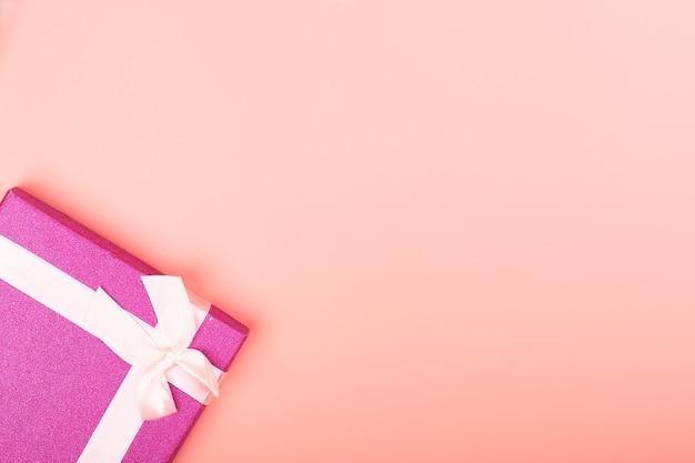 ピンクの背景にリボンが付いたピンクのキラキラギフトボックス。テキスト用の空のスペースを持つ最小限の背景