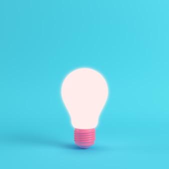 Розовая светящаяся лампочка на ярко-синем фоне
