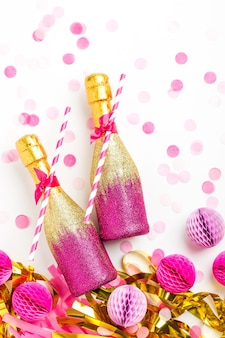 Pink and gold mini bottles of champagne with confetti and tinsel. flat lay.