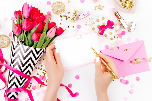 Pink and gold styled desk with florals. female hands hold card