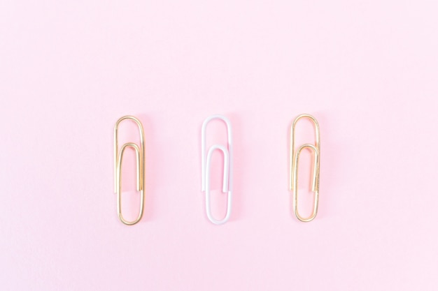 Pink and golden paper clips on a pastel pink background.