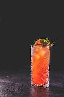 ダークエレガントな背景にハイボールグラスのピンクグレープフルーツメスカルパロマカクテル